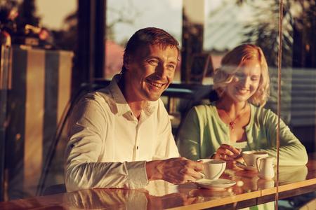 hombre tomando cafe: Reuni�n de los pares adultos en cafeter�a Foto de archivo