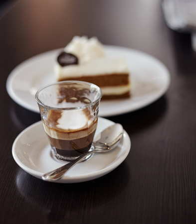 cau: Coffee mochiatto in glass cau and cake on the table in cafe Stock Photo