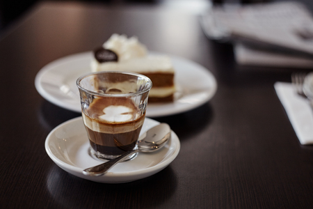 coffee and cake: Coffee mochiatto in glass cau and cake on the table in cafe Stock Photo