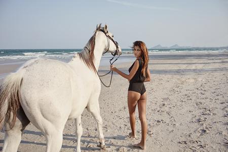 Aziatisch vrouwelijk model met witte paard op de kust lijn