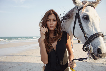 sexual activities: Asian female model with white horse on the sea coast line