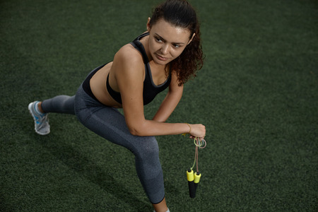 saltar la cuerda: Young woman in sports wear doing exercises at the open stadium with jump rope