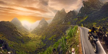 motociclista: A la monta�a paisaje con el camino asfalto y motociclista en el movimiento. imagen de la manipulaci�n digital