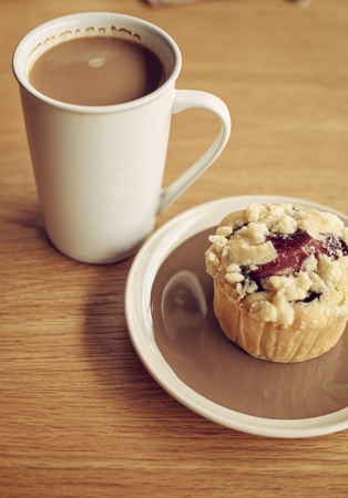 blueberry muffin: Coffee in mug and blueberry muffin on the wooden table