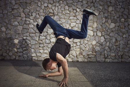 head down: Young man dancing and balancing head down on the land in the city