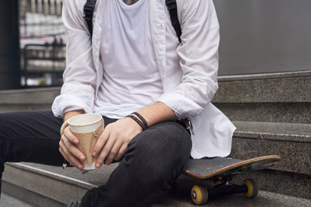 young male model: Young male model in wwhite shirt sitting with coffee cup on the stair in downtown Stock Photo