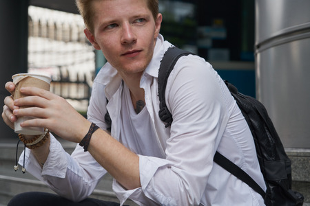 stressing: Young male model in wwhite shirt sitting with coffee cup on the stair in downtown Stock Photo