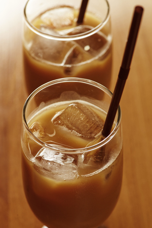 macchiato: Two glass iced coffee latte wwith ice and straw incide placed on wood tale