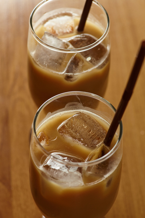 Two glass iced coffee latte wwith ice and straw incide placed on wood tale