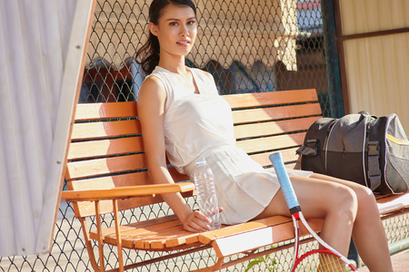 Young beautifull sport woman relaxing with water on the bench at the tennis court after game