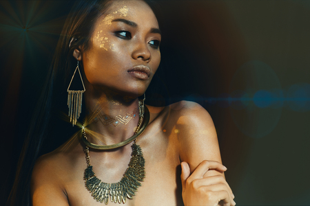 flare up: Close up female model with dark skin, golden style necklace and braseletes golden makeup  in lens flare and tonned colors Stock Photo