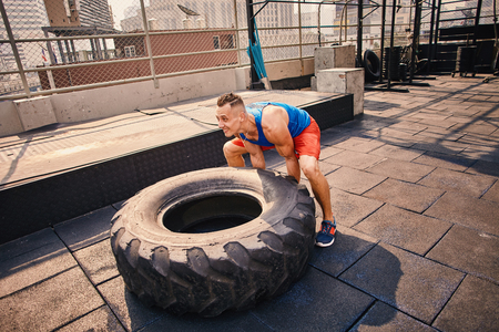 Male fitness model training workout witth heavy and big tire at the outdoor fitness center