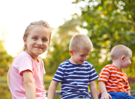 Group of children boys and girl enjoing together on the bench at the country side
