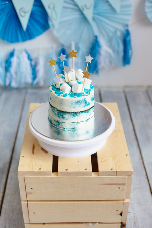 Home hand made cake with blue cream on the wooden bo against colored flags