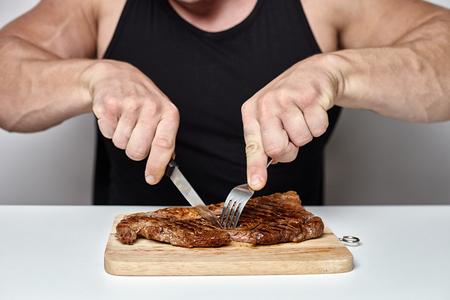 큰 몸을 닫습니다 보디 빌딩 테이블 반대 회색 벽 뒤에 큰 쇠고기 스테이크를 먹으십시오