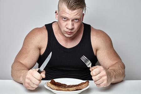 間近で身体の大きなボディービルダー灰色の壁の反対側のテーブルの後ろの大きなステーキを食べる