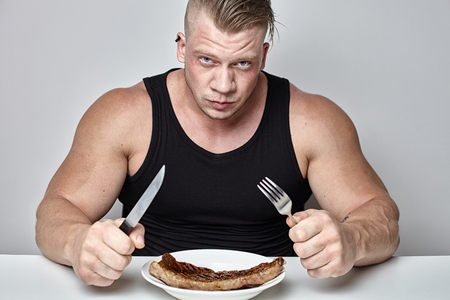 Close up big body bodybuilder eat big beef steak behind table opposite gray wall