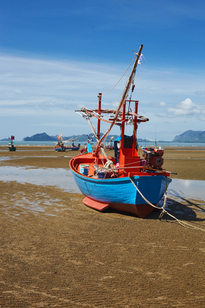 Fishing boat at the sea coast in sea low tide under blue sky Stock Photo