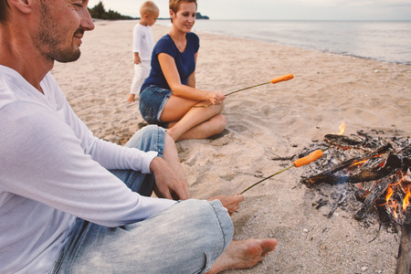 Evening picnic sausages barbeque with bonfire at the seacoast sand Stock Photo