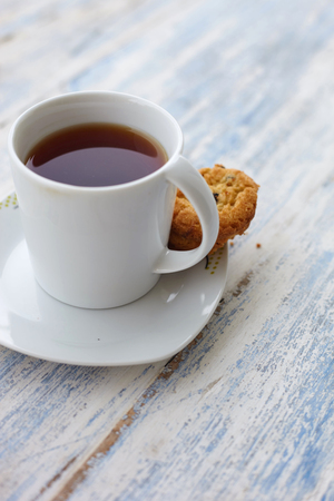 Close up cup of tea with cookes on the woooden rural table