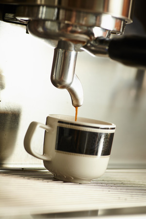 Close up small coffee cup under coffee machine drip coffee espresso into cup