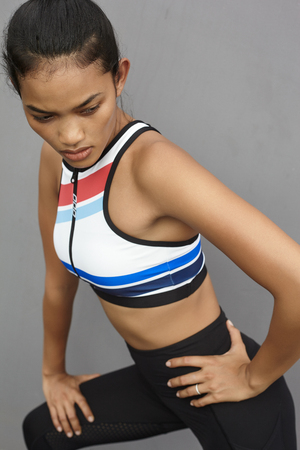 Fashion portrait female model in leggings and sports wear opposite gray wall
