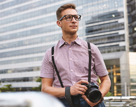 Porttrait young male model in glasses with diggital camera at the city outdoor