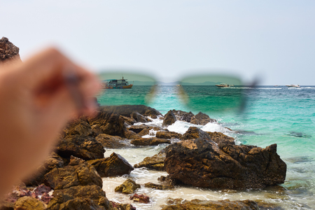 Close up and out of focus sunglasses in arm with polarized effect for the sea with speed boates