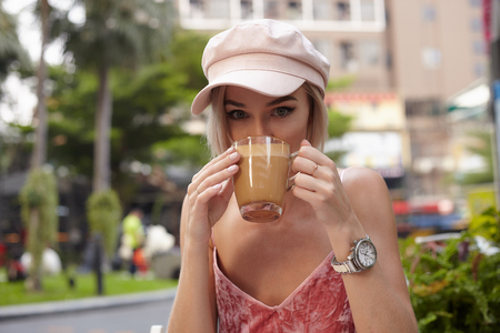 Young female model in street cafe with cup of coffee