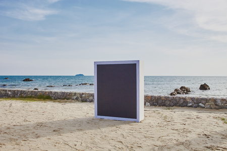 Black board for text and design placed at the beach under evening sunlight