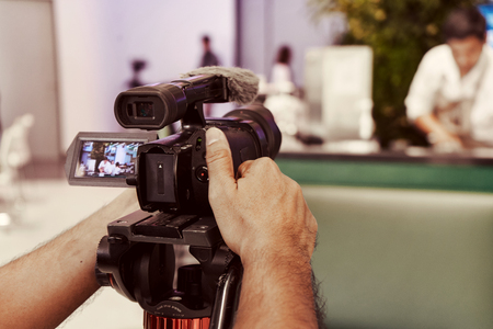 Back view to the camera and cameraman hands shoot documentary video