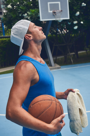 Male basketball player portrait next to the court relaxing after game in hot sweat