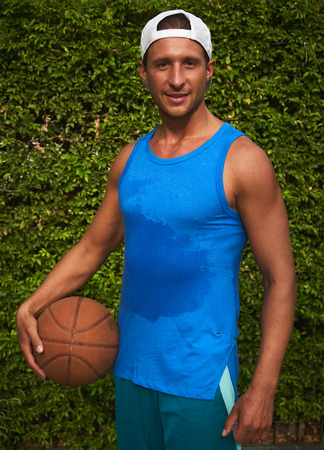 Portrait young guy basketball player in hat with ball and swet tank top after training opposit green bush Stock Photo
