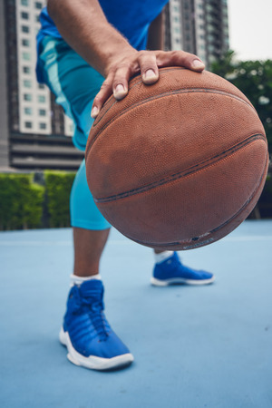 Basketball player close up shot with ball at the bascetball court outside in city 版權商用圖片 - 126266276