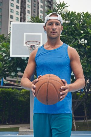 Basketball player close up shot with ball at the bascetball court outside in city Stock Photo