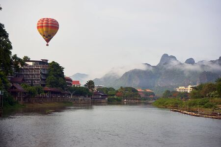 Laos, Van Vieng city landscape with river and mountains with flying balloon at the sky 版權商用圖片 - 128225097