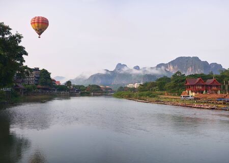 Laos, Van Vieng city landscape with river and mountains with flying balloon at the sky