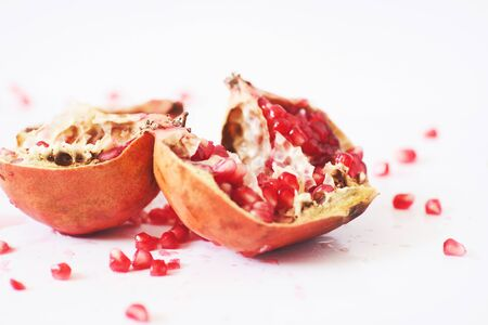 Crushed pomegranate with seeds placed on white background                               版權商用圖片
