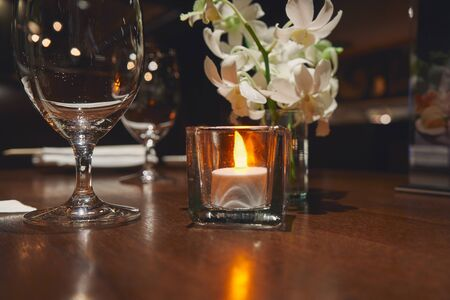 Close up table set sceen with candle light flowers and wine glass at the dark restaurant space