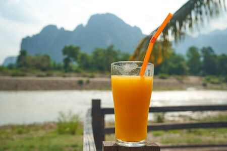 Mango fresh coctail in glass opposit mountain view background with river 版權商用圖片 - 128225349