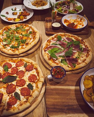 Pizza and other dishes on the wood table food style