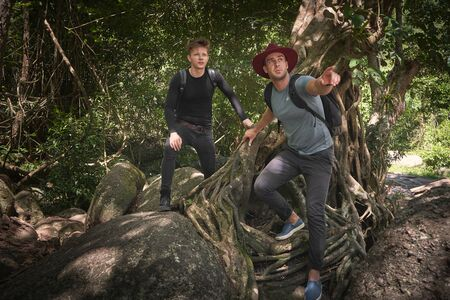 Two male travelers hitchhiking at the rock and forest in adventure 版權商用圖片 - 128234931