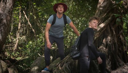 Two male travelers hitchhiking at the rock and forest in adventure 版權商用圖片