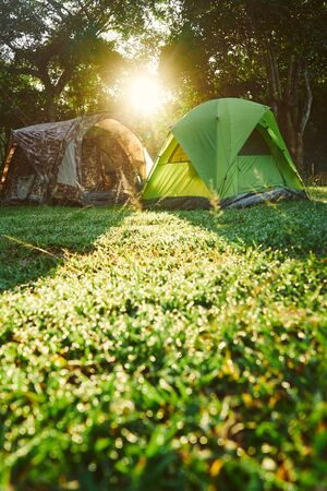 Camping tent at the background with morning sunlight and green grass 版權商用圖片 - 128572790