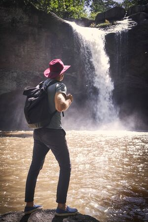 Man in hat with backpack stand on the rock against waterfall streaam in rain season