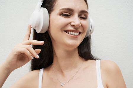 Young woman wearing classic style casual clothes with headphone opposite gray background