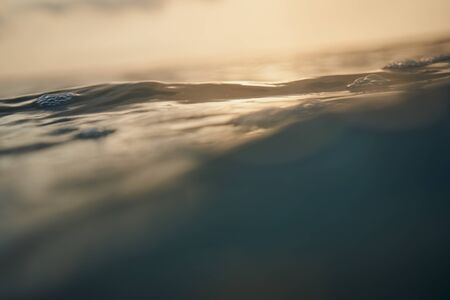 Close up ocean wave under bueatiful sunlight with lens cretive effects