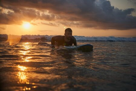 Male surfer getting ready for ride on the ocean wave against beautifull sinset light