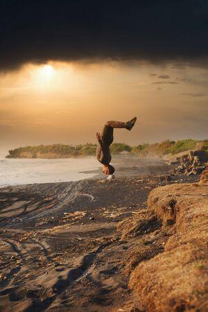 Freestyler sportsman do back flip at the ocean beach at sunset time