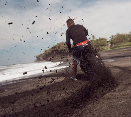 Man ride on the motorbike at the ocean black sand beach